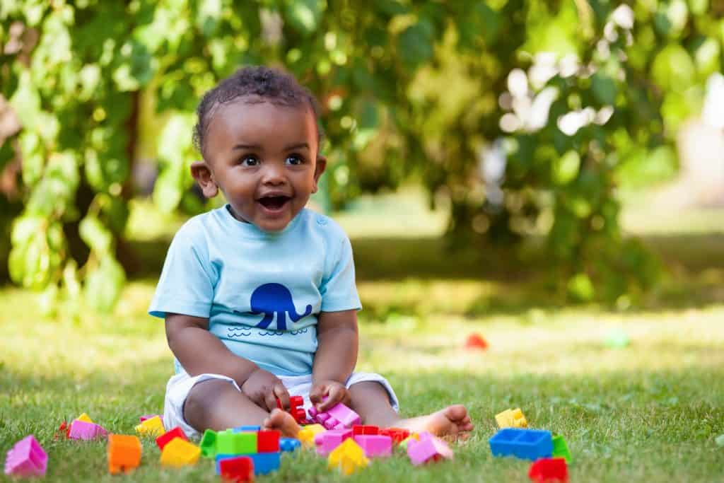 Baby playing blocks in grass